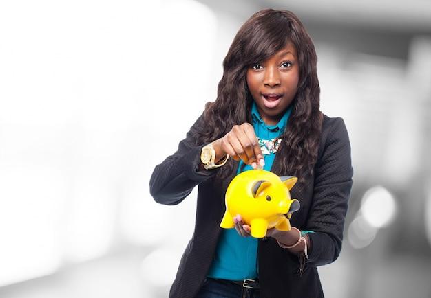 Mulher com um banco piggy amarelo nas mãos