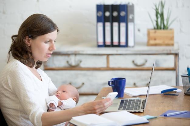 Mulher com um bebê que olha seu telefone
