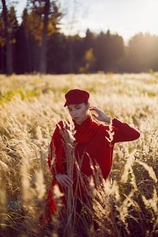 Mulher com um boné de suéter vermelho e lenço em pé em um campo no outono na grama alta e seca