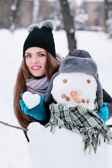 Mulher com um boneco de neve e uma bola de neve em forma de coração