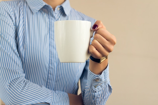 Mulher, com, um, borgonha, manicure, em, um, azul, camisa listrada, segura, um, branca, copo