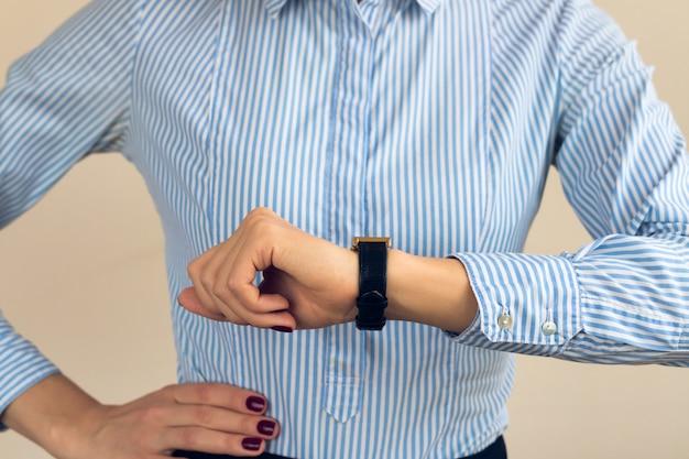 Mulher, com, um, borgonha, manicure, em, um, camisa listrada azul, olhar tempo, ligado, relógio mão, closeup