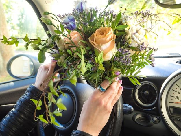 Mulher com um buquê de flores, dirigindo um carro.