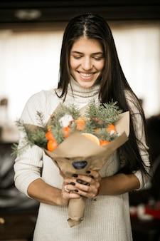 Mulher com um buquê de frutas no natal