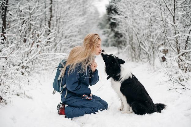 Mulher com um cachorro border collie preto e branco na neve