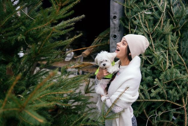Mulher com um cachorro branco nos braços perto de uma árvore de natal verde no mercado