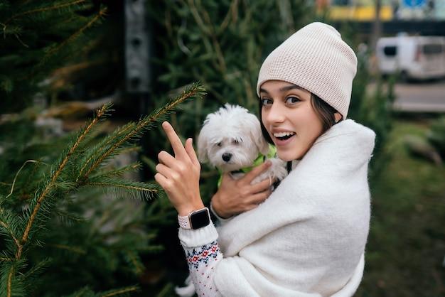 Mulher com um cachorro branco nos braços perto de uma árvore de natal verde
