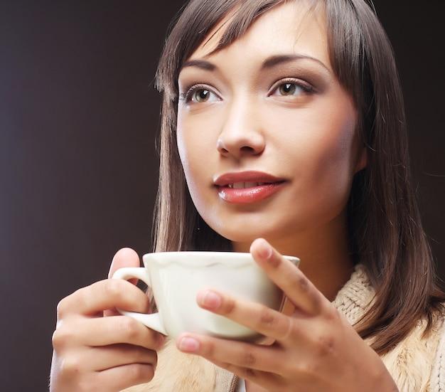 Mulher com um café aromático nas mãos