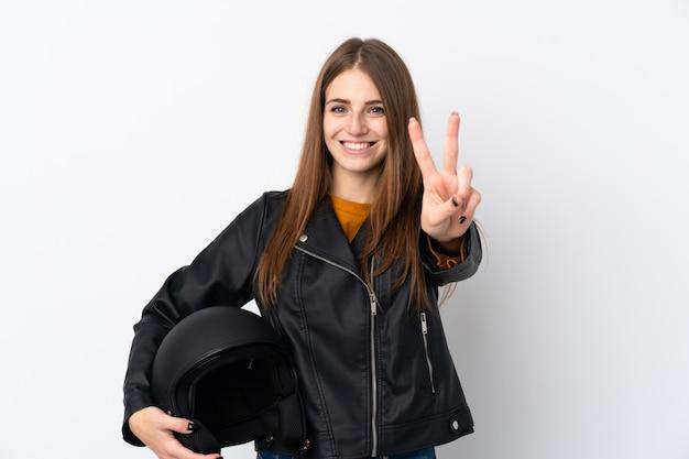 Mulher com um capacete de moto sorrindo e mostrando sinal de vitória