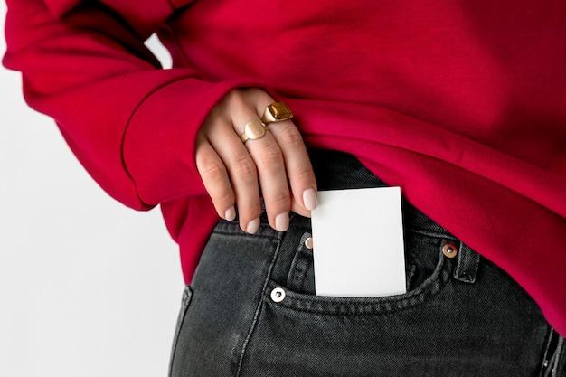 Mulher com um cartão branco no bolso da calça jeans