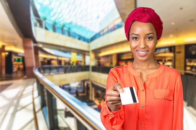 Mulher com um cartão de crédito no shopping