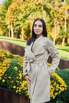 Mulher com um casaco bege caminha no parque outono