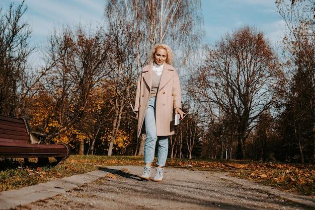 Mulher com um casaco de outono segurando um livro