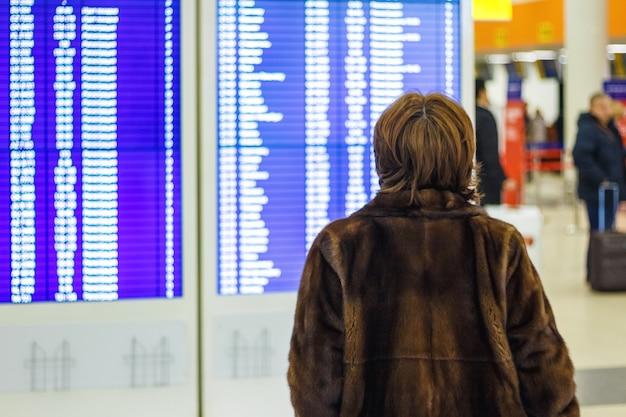 Mulher com um casaco de pele olhando o horário no aeroporto