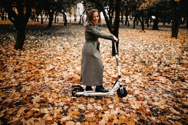 Mulher com um casaco no outono em uma scooter elétrica em um parque de outono andando em veículos elétricos