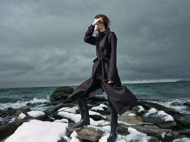 Mulher com um casaco preto ao ar livre paisagem oceano nuvens escuras gótico