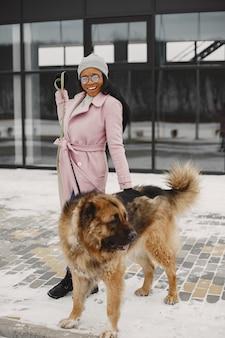 Mulher com um casaco rosa com cachorro
