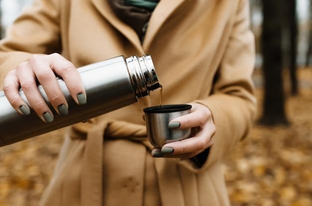 Mulher com um casaco serve chá de uma garrafa térmica, ao ar livre. close-up de mãos femininas e uma caneca com chá.