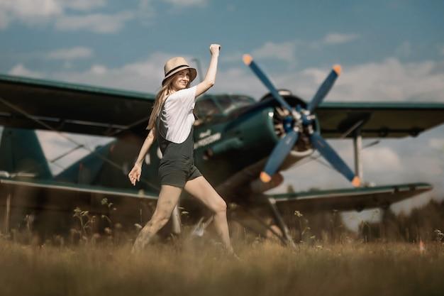 Mulher com um chapéu de palha no fundo, posando no cenário de um avião com uma hélice