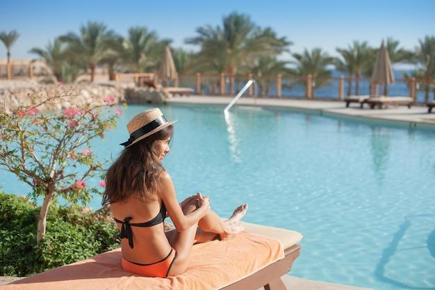 Mulher com um chapéu de palha relaxando em um sofá-cama perto de um luxuoso hotel de verão com piscina no egito, o conceito de tempo para viajar.