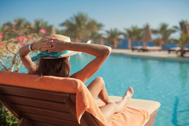 Mulher com um chapéu de palha relaxando perto de uma luxuosa piscina de verão