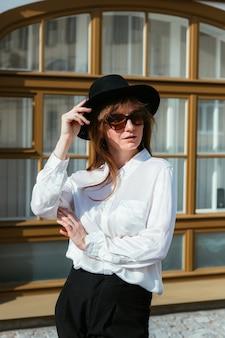 Mulher com um chapéu e óculos escuros posando no contexto de uma bela fachada