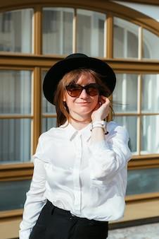 Mulher com um chapéu e óculos escuros posando sorrindo no fundo de uma bela fachada