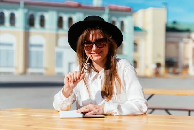 Mulher com um chapéu e óculos escuros sorrindo enquanto está sentada em um café com um lápis e um bloco de notas nas mãos