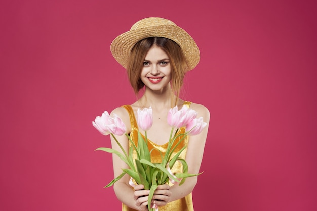 Mulher com um chapéu e um buquê de flores como um presente no feriado do dia dos namorados