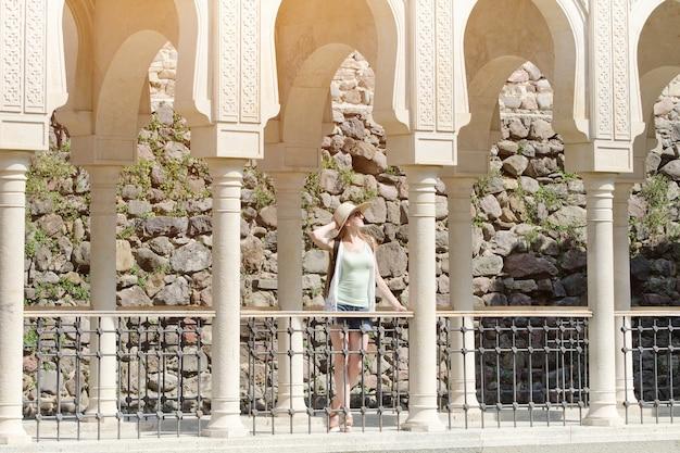 Mulher com um chapéu em pé entre as colunas. dia ensolarado