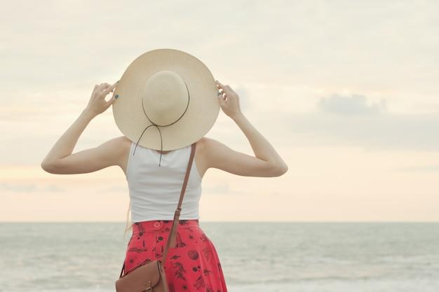 Mulher com um chapéu ficar à beira-mar, pôr do sol. vista traseira