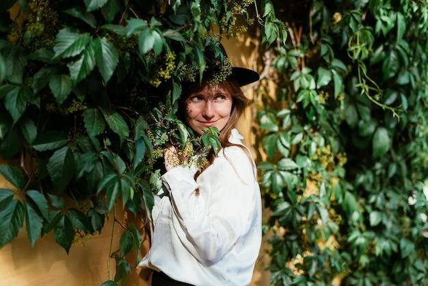 Mulher com um chapéu perto de um velho muro com folhas penduradas