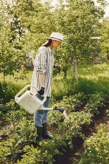 Mulher com um chapéu segurando um funil e trabalhando em um jardim