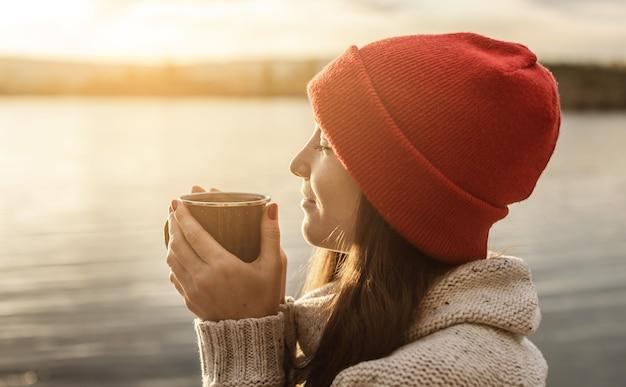 Mulher com um chapéu vermelho está bebendo café no lago ao pôr do sol. recreação ao ar livre de outono
