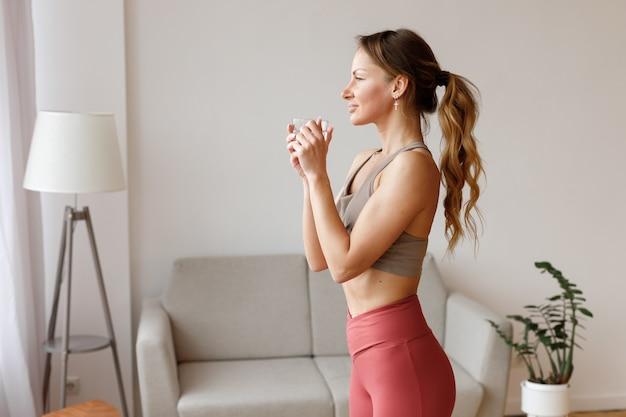 Mulher com um copo de água depois de um treino em casa na sala de estar