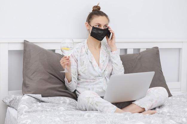 Mulher com um copo de água trabalhando em casa e usando máscara protetora.