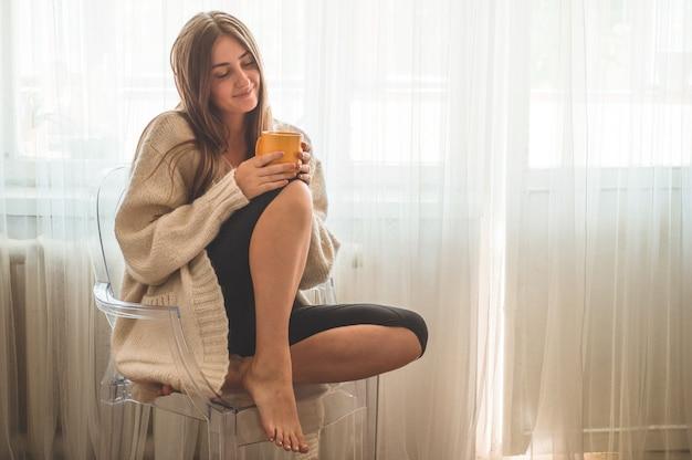 Mulher com um copo de bebida quente perto da janela. bom dia com chá. outono inverno