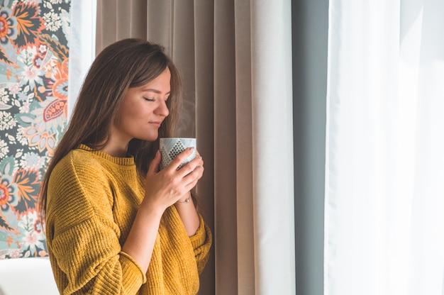 Mulher com um copo de bebida quente perto da janela. olhando para a janela e beber chá. bom dia com chá. outono inverno