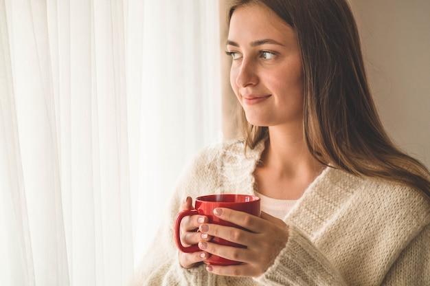 Mulher com um copo de bebida quente perto da janela