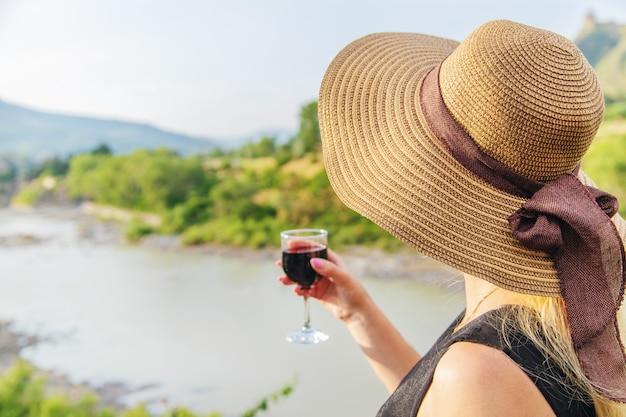 Mulher com um copo de vinho contra o pano de fundo das montanhas da geórgia