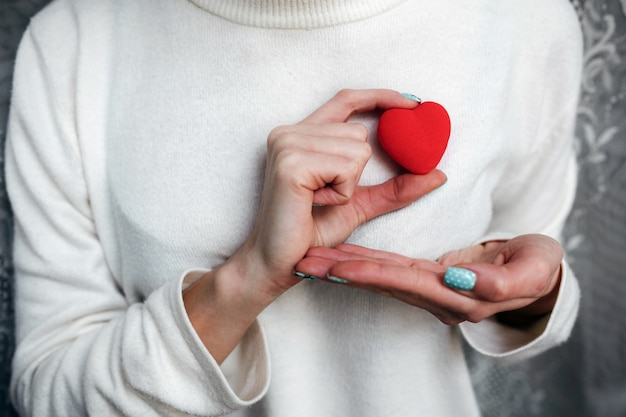 Mulher com um coração vermelho na mão