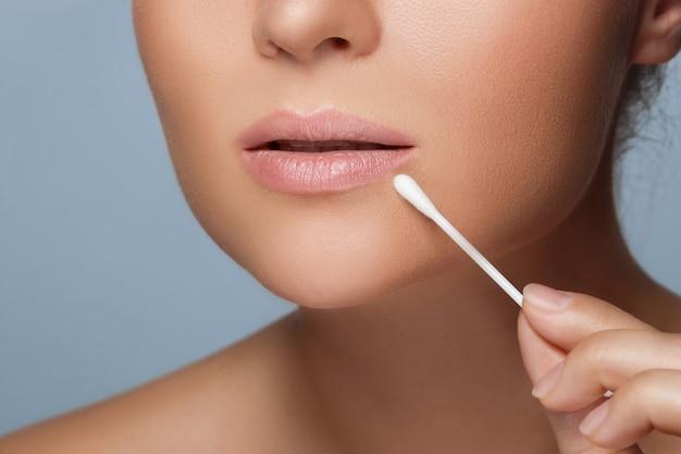 Mulher com um cotonete ao lado dos lábios