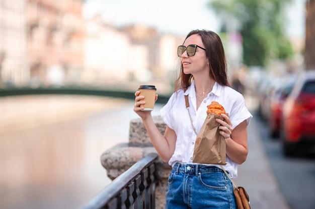 Mulher com um croissant e café ao ar livre no passeio