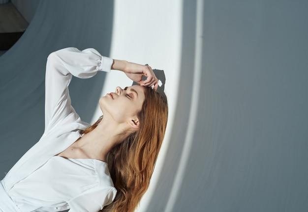 Mulher com um fundo claro com roupas brancas maquiagem cabelo ruivo