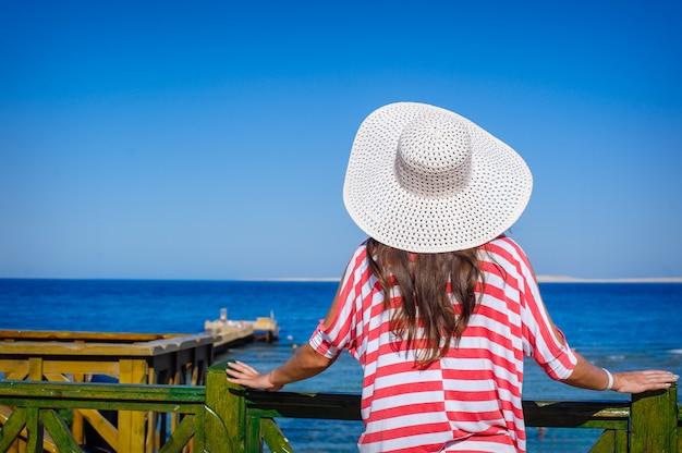 Mulher com um grande chapéu branco olha para o mar