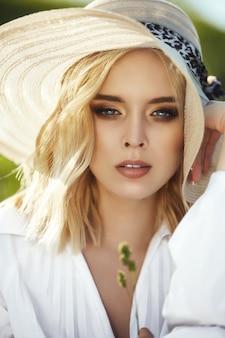 Mulher com um grande chapéu e um vestido longo branco está sentado na grama em um campo. mulher loira ao sol em um vestido leve. mulher descansando e sonhando, maquiagem perfeita de verão no rosto