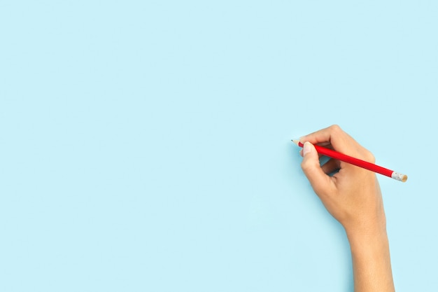 Mulher com um lápis em um fundo azul claro com espaço de cópia