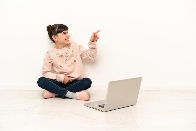 Mulher com um laptop sentada no chão apontando o dedo para o lado