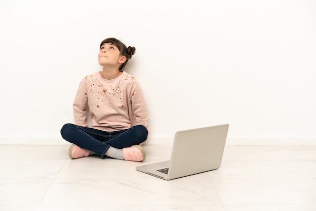 Mulher com um laptop sentada no chão olhando para cima