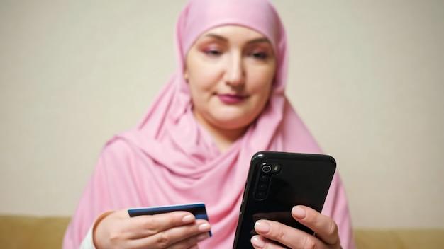 Mulher com um lenço rosa faz compras online no telefone com um cartão do banco nas mãos.
